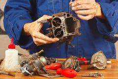 Reparatie van details oude automobiele motor in workshop Stock Foto