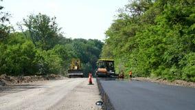 Reparatie van een een weg, machine van de rolpers en een asfaltafwerker die een nieuwe verse asfaltbestrating leggen, die op beha stock footage