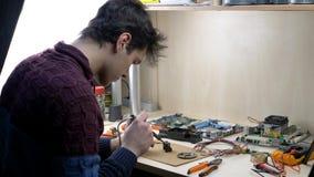 Reparatie van elektronische apparaten, tin solderende delen stock footage