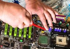 Reparatie van PC-motherboard met een schroevedraaier met een rood handvat stock foto's