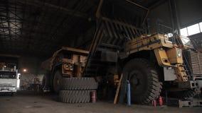 Reparatie van stortplaatsvrachtwagens in grote garage open kuil stock footage