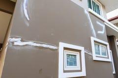 Reparatiebarst op huismuur met het pleister van de laagjedeklaag royalty-vrije stock foto