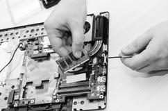 Reparatielaptops, close-up van handen en ontmantelde oude computer Ð'lack en witte fotografie stock afbeelding