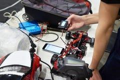 Reparatieradio gecontroleerde auto en meester met kenmerkend apparaat stock foto