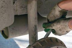 Reparation av bilupphängningen behandskad hand Utbytning av stötdämparestöttan royaltyfri bild