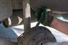 Reparation av bilupphängningen behandskad hand Utbytning av stötdämparestöttan arkivbilder