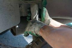 Reparation av bilupphängningen behandskad hand Utbytning av stötdämparestöttan royaltyfria bilder