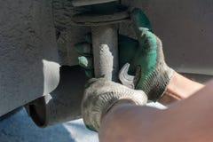 Reparation av bilupphängningen behandskad hand Utbytning av stötdämparestöttan arkivfoto