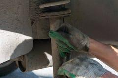 Reparation av bilupphängningen behandskad hand Utbytning av stötdämparestöttan royaltyfri foto
