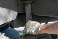 Reparation av bilupphängningen behandskad hand Utbytning av stötdämparestöttan arkivbild