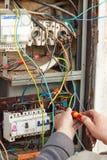 Reparation av den gamla elektriska switchgearen En elektriker byter ut gamla elektriska ledningsnätapparater Royaltyfri Bild