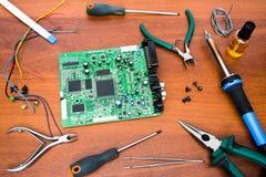 Reparation av det elektroniska systembrädet med microcircuits och elektroniska delar nödvändiga hjälpmedel Arkivbild