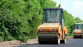 Reparation av en huvudväg, rullcompactormaskin, asfaltefterbehandlare som lägger en ny ny asfalttrottoar som täcker på en arkivfilmer