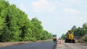 Reparation av en huvudväg, en rullcompactormaskin och en asfaltefterbehandlare som lägger en ny ny asfalttrottoar som täcker på e stock video