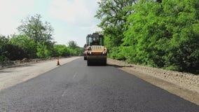 Reparation av en huvudväg, en rullcompactormaskin och en asfaltefterbehandlare som lägger en ny ny asfalttrottoar som täcker på e arkivfilmer