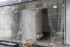 Reparation av ett modernt rum med glasväggar och ingångsdörrar Konstruktion och design av en handelplattform målande arbeten Betr royaltyfria bilder