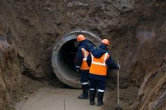 Reparation av stadsvattenförsörjning Utbyte av gamla rostiga metallrör på plast- rör Nya moderna teknologier av stads- teknik n royaltyfri bild