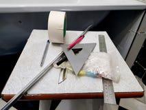 Reparation - byggnad med hj?lpmedel, m?ttband, blyertspenna, penna, mark?r, maskeringstejp, triangel, h?rn, tegelplattah?rn, alum arkivfoto