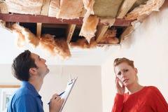 Reparation för byggmästareAnd Customer Discussing tak Arkivbild