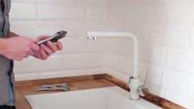 Reparation för sanitär teknik av vattenläckage man som fixar en vattenkran i köket arkivfilmer