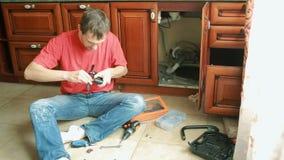 Reparation för sanitär teknik av vattenläckage man som fixar en vattenkran i köket lager videofilmer