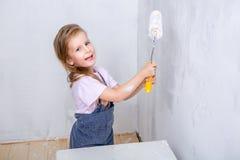Reparation i lägenheten Den lyckliga den familjmodern och dottern i förkläden målar väggen med vit målarfärg hållande målarfärgru royaltyfri bild
