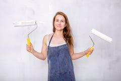 Reparation i lägenheten Den lyckliga familjmodern och den lilla dottern i blåa förkläden målar väggen med vit målarfärg Mamman ry arkivfoton