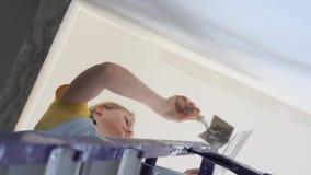 Reparation i lägenheten - en ung kvinna av det europeiska utseendet gör reparationer hemma stock video
