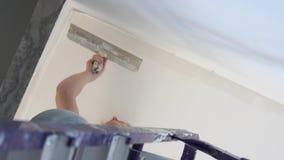 Reparation i lägenheten - en ung kvinna av det europeiska utseendet gör reparationer hemma arkivfilmer