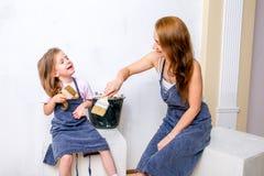 Reparation i lägenheten Lycklig familjmoder och dotter i förberedda förkläden som målar väggen med vit målarfärg Sitt med borstar arkivbilder