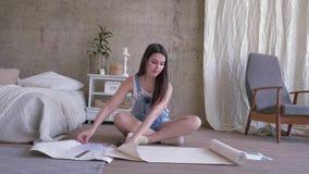 Reparation och inre rum som ler flickan i grov bomullstvilloveraller som mäter tapeten med måttbandet på golv på lägenheten
