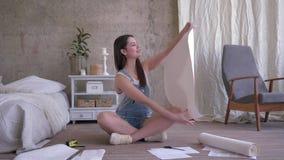 Reparationen i ny lägenhet, den härliga lyckliga unga kvinnan ser på ett klippt stycke av tapeten som sitter på golv på bakg