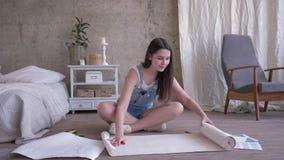 Reparationen och hemförbättring, flickan med blyertspennan och måttbandet gör fläckar på ny tapetrulle på golv