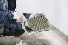 reparationer Lägga av keramiska tegelplattor för golv Händer för man` s i handskar med spateln, spridningcementmortel på den kera royaltyfri foto