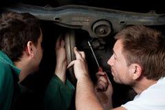 Reparationsbil för två auto mekaniker i auto service Arkivfoto