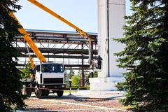 Reparationskolonner på en special teknik Arbetare på kranen reparerar en stor vit kolonn Kosmetisk reparation med målning arkivfoto