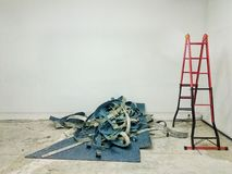 Reparatur arbeitet im Büro, in einem Bündel abgestreiftem Teppich auf dem Boden und in einer Leiter, Arbeitsfluß Stockfotografie