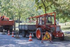 Reparatur auf der Straße, gibt es ein Stoppschild und einen Traktor lizenzfreie stockfotografie