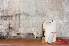 Reparatur der alten Betonmauer des Raumes, des schmutzigen braunen Bodens und der Werkzeuge Lizenzfreie Stockfotografie
