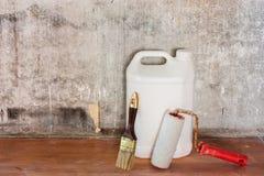 Reparatur der alten Betonmauer des Raumes, des schmutzigen braunen Bodens und der Werkzeuge Lizenzfreies Stockbild