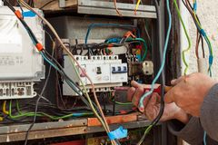 Reparatur der alten elektrischen Schaltanlage Ein Elektriker ersetzt alte elektrische Verdrahtungsgeräte Lizenzfreie Stockbilder