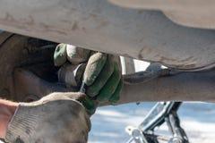 Reparatur der Autosuspendierung Behandschuhte Hand Ersetzen der Stoßdämpferspreize lizenzfreies stockfoto