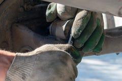 Reparatur der Autosuspendierung Behandschuhte Hand Ersetzen der Stoßdämpferspreize stockfotos