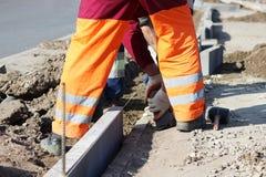 Reparatur des Bürgersteigs Berufsarbeitsmaurer im Overall legen Beschränkungen, bevor sie Pflastersteine des Steins legen Stockfotografie