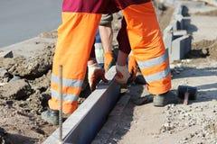 Reparatur des Bürgersteigs Berufsarbeitsmaurer im Overall legen Beschränkungen, bevor sie Pflastersteine des Steins legen Lizenzfreie Stockbilder