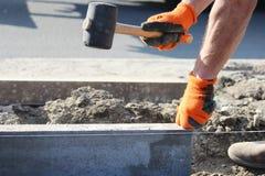 Reparatur des Bürgersteigs Berufsarbeitsmaurer im Overall legen Beschränkungen, bevor sie Pflastersteine des Steins legen Lizenzfreie Stockfotografie