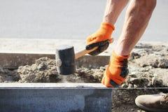 Reparatur des Bürgersteigs Berufsarbeitsmaurer im Overall legen Beschränkungen, bevor sie Pflastersteine des Steins legen Stockbild