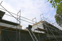Reparatur des Gebäudes, der Bausesselbahn und des Baugerüsts stockfotos