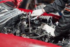 Reparatur des modernen Dieselmotors, der Arbeitskrafthände und des Werkzeugs Nahaufnahme eines Automechanikers, der an einem Auto Stockbild