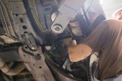 Reparatur- und Kontrollauto in der Reparaturwerkstatt Ein erfahrener Techniker repariert das fehlerhafte Teil des Autos Ich ?nder stockfotografie